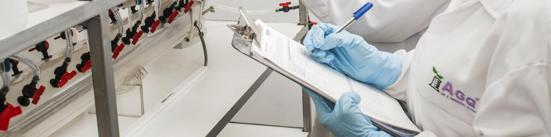 Trabajadores de AGQ Labs apuntado datos en un laboratorio